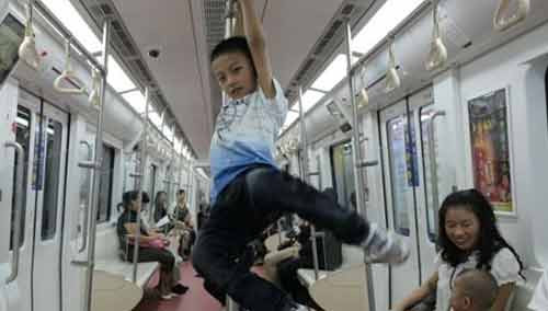 """广州:地铁扶杆当单杠 父子试玩""""高难度"""""""