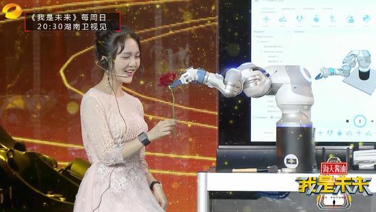 机械臂给未来体验官上完妆之后献上一支玫瑰